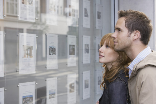 Young couple looking in an eastate agents window