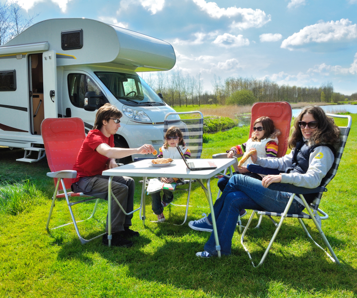 Family sitting at a table in front of their motorhome