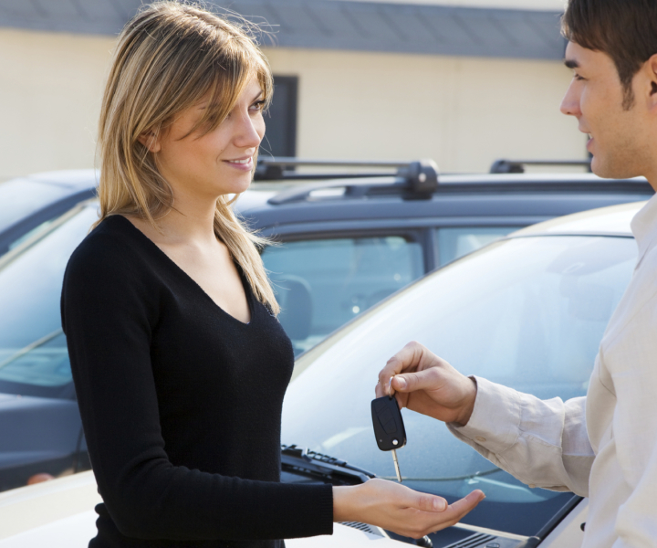 Woman accepting car keys from a salesman