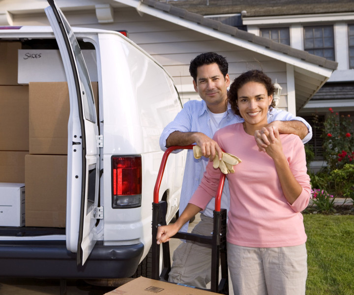 Couple standing behind a van loaded with boxes