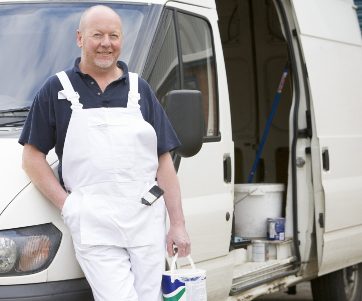Tradesman leaning on a white van