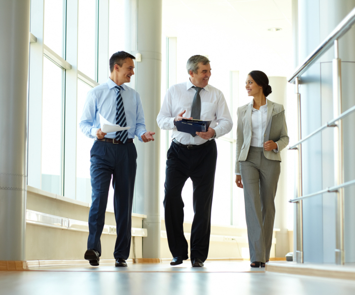 Three business people walking in an office