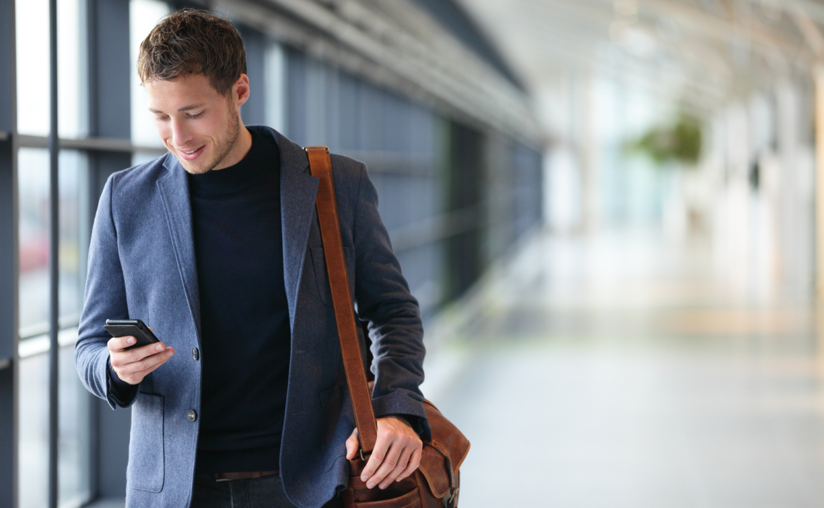 Man in airport with bag and using a phone