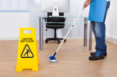 Wet floor sign and man mopping the floor