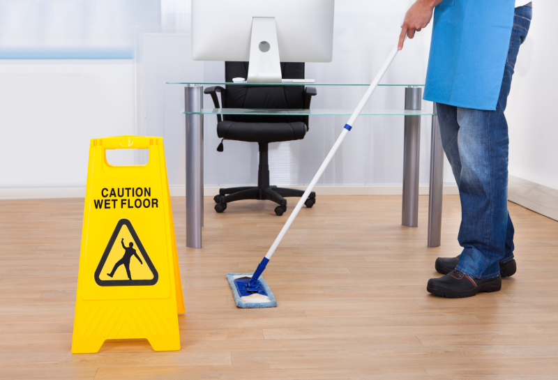 Man mopping the floor with and a wet floor sign